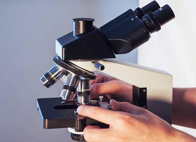 Nahaufnahme von wissenschaftlerhänden mit dem mikroskop, proben überprüfend.