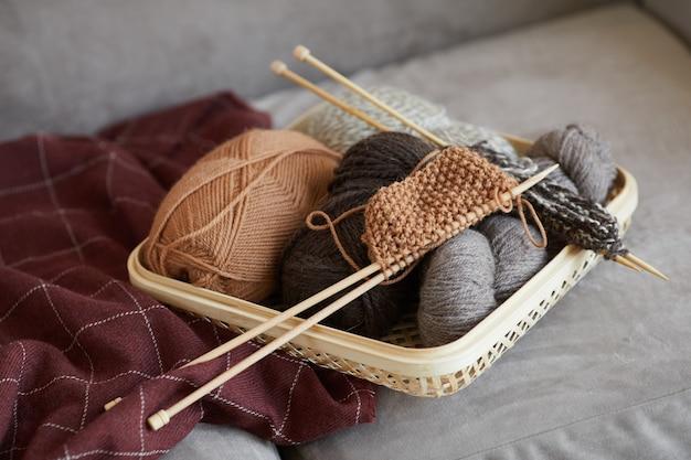 Nahaufnahme von wolle und nadeln zum stricken auf dem sofa