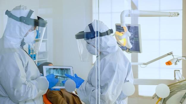 Nahaufnahme von zahnarztärzten mit gesichtsschutz und ppe-anzug, die im zahnarztraum über digitales röntgen der zähne diskutieren, während der patient wartet. konzept des neuen normalen zahnarztbesuchs bei ausbruch des coronavirus.