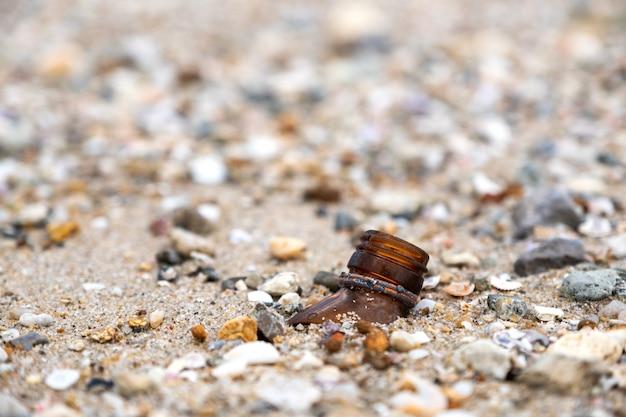 Nahaufnahme von zerbrochenen flaschen am strand