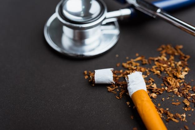 Nahaufnahme von zerbrochenen haufen zigarette oder tabak und arzt stethoskop
