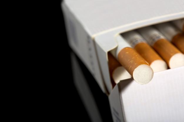 Nahaufnahme von zigaretten in der packung. isoliert auf schwarz