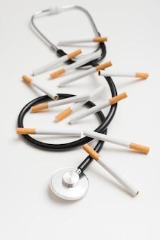 Nahaufnahme von zigaretten und von stethoskop über weißem hintergrund