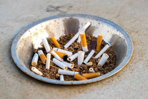 Nahaufnahme von zigarettenkippen in metallaschenbecher auf der straße. konzept vieler zigarettenreste nach dem rauchen.