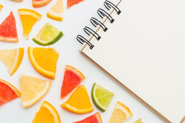Nahaufnahme von zitrusfruchtscheiben mit gewundenem notizblock