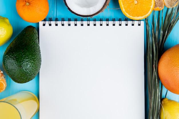 Nahaufnahme von zitrusfrüchten als mandarinen-avocado-kokosnuss-zitrone und zitronensaft mit notizblock in der mitte auf blauem hintergrund mit kopienraum