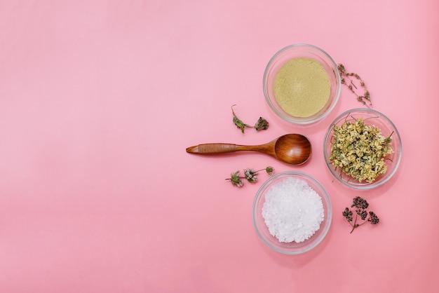 Nahaufnahme von zutaten der ayurvedischen behandlung oder gesichtspackung. gelber ton, kurkumapulver und getrocknete kamille, grobes meersalz in glasbechern auf einem rosa pastellfarbenen hintergrund.