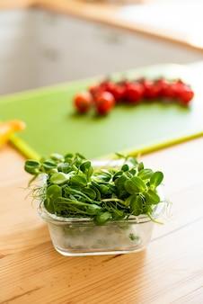 Nahaufnahme von zutaten für einen gesunden sommersalat mit microgreens. im hintergrund wird eine kirschtomate geschnitten