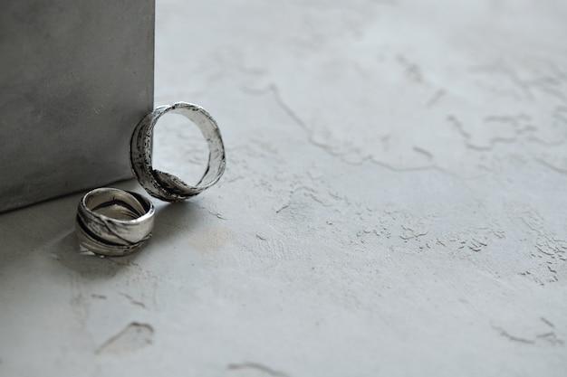 Nahaufnahme von zwei breiten silbernen ringen auf der gipsoberfläche, einer von ihnen lehnt sich auf die box