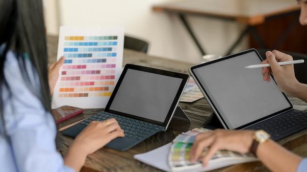 Nahaufnahme von zwei designern, die farbe für ihr projekt im gemeinsamen arbeitsraum auswählen