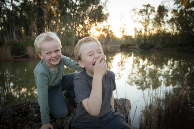 Nahaufnahme von zwei entzückenden australischen kleinen jungen, die auf einem fluss lachen?
