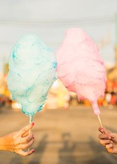 Nahaufnahme von zwei frauen, die süßigkeitsglasschlacke halten