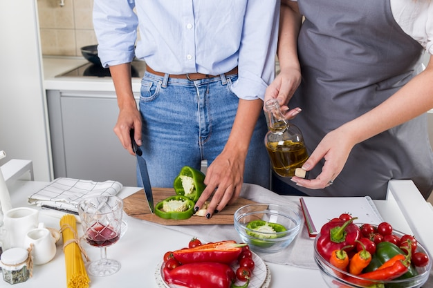 Nahaufnahme von zwei frauen, die zusammen das lebensmittel in der küche zubereiten