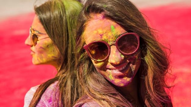 Nahaufnahme von zwei frauen, welche die sonnenbrille bedeckt mit holi farbpulver tragen