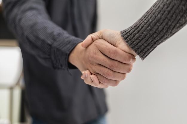Nahaufnahme von zwei geschäftsleuten, die händchen halten, zwei geschäftsleute einigen sich auf geschäfte und schütteln sich nach einer erfolgreichen verhandlung die hände. händeschütteln ist ein westlicher gruß oder glückwunsch.