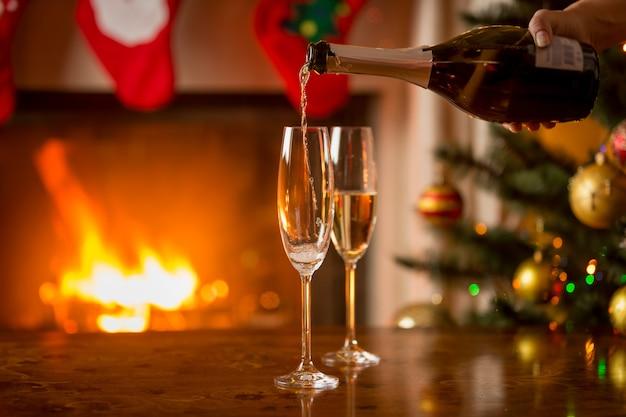 Nahaufnahme von zwei gläsern champagner neben dem kamin