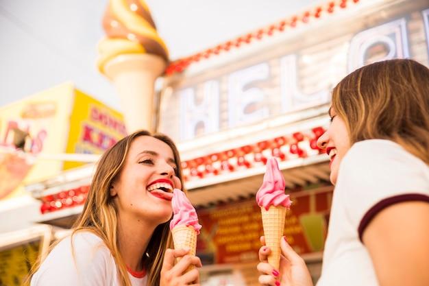 Nahaufnahme von zwei glücklichen freundinnen, die eiscreme essen