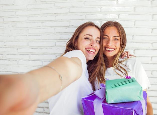 Nahaufnahme von zwei glücklichen freundinnen mit geburtstagsgeschenken