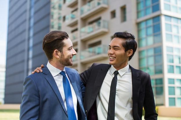 Nahaufnahme von zwei glücklichen kollegen umarmen draußen