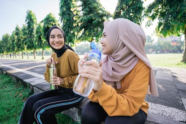 Nahaufnahme von zwei glücklichen muslimischen mädchen nach dem gemeinsamen sport am nachmittag, wenn sie das fasten brechen und wasser mit flaschen im park trinken