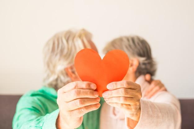Nahaufnahme von zwei glücklichen und verliebten senioren, die sich lächeln und küssen und ein rotes herz zusammenhalten - reife menschen, die sich an der kamera verlieben, die ein rotes herz zusammenhalten - reife verliebte menschen