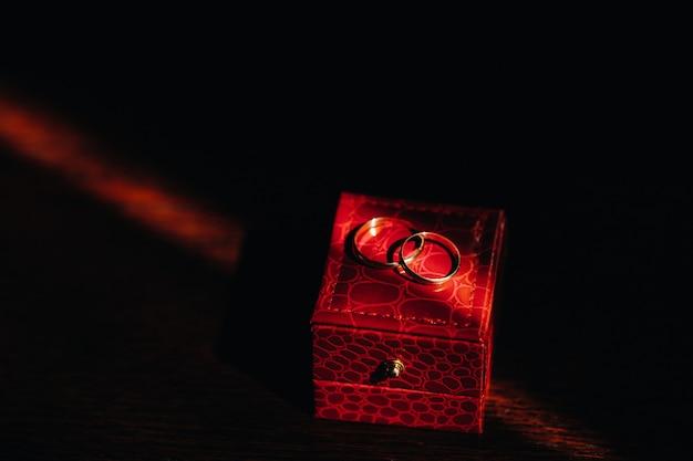 Nahaufnahme von zwei goldenen eheringen für die hochzeit liegen auf einer roten box.