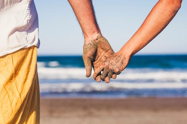 Nahaufnahme von zwei händen, die sich am strand zusammenhalten, mit den händen schmutzig vom sand - urlaub im freien in beziehung