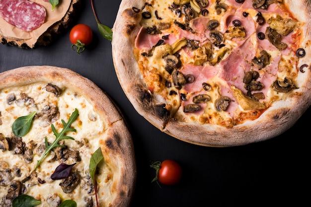 Nahaufnahme von zwei italienischer pizza mit verschiedenen belägen und kirschtomate