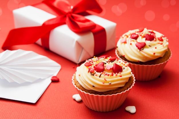 Nahaufnahme von zwei kleinen kuchen mit sahne und herzdekor auf einer roten oberfläche mit geschenk und umschlag.