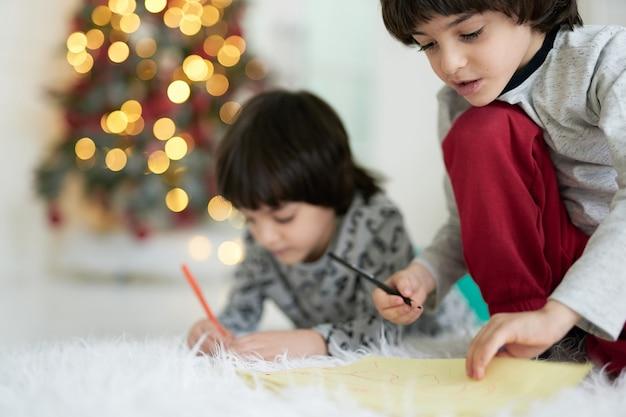 Nahaufnahme von zwei kleinen lateinamerikanischen jungen, zwillinge, die zeichnen, während sie zu hause auf dem boden sitzen und weihnachtlich dekoriert sind. geschwister, die gemeinsam kreativ tätig sind