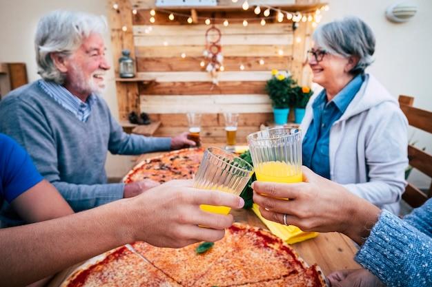 Nahaufnahme von zwei klirrenden gläsern und zwei senioren, die im hintergrund sprechen - familie, die auf der terrasse des hauses mit zwei bekannten pizzen isst