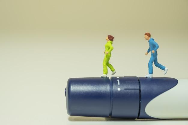 Nahaufnahme von zwei läufer-miniaturfiguren, die auf lanzette laufen, um blutzuckerspiegel zu überprüfen