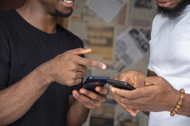 Nahaufnahme von zwei männern, die inhalte mit ihren telefonen teilen