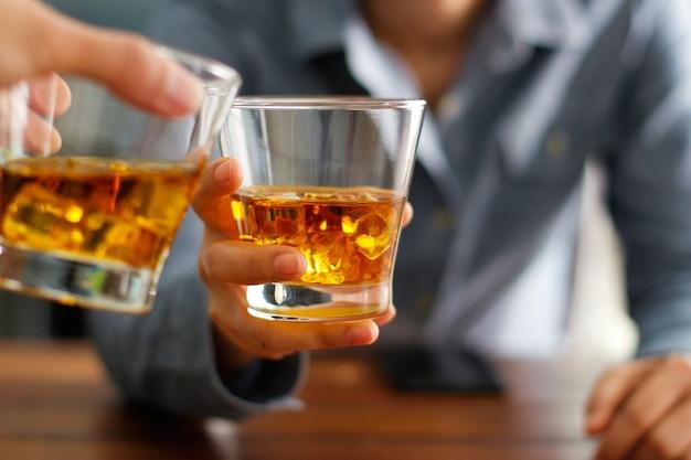 Nahaufnahme von zwei männern klirren gläser alkoholisches getränk des whiskygetränks zusammen