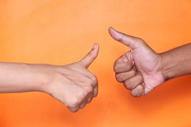 Nahaufnahme von zwei personenhand, die einen daumen nach oben zeigt