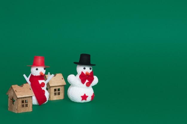 Nahaufnahme von zwei schneemännern und kleinen holzhäusern als weihnachtsschmuck auf grünem hintergrund