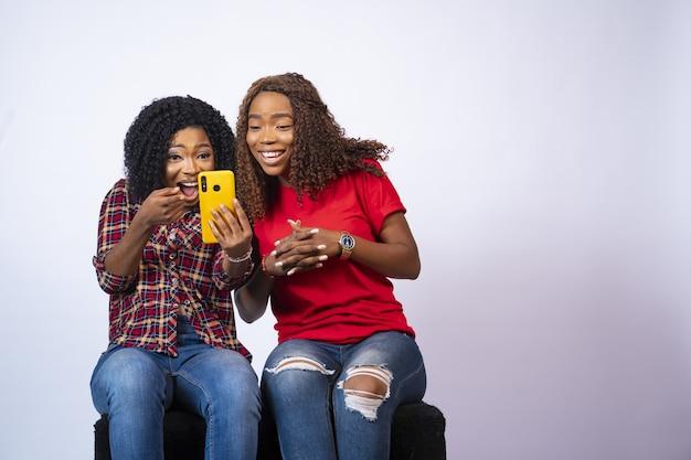 Nahaufnahme von zwei schönen schwarzen frauen, die aufgeregt schauen, während inhalt zusammen auf einem telefon betrachten