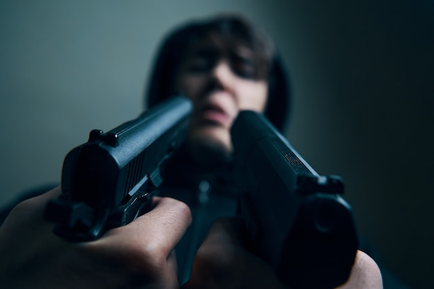 Nahaufnahme von zwei waffen, die auf das vernarbte gesicht eines mannes gerichtet sind, der einen mann in einer kapuze mit pistolen-drohungen verhört...