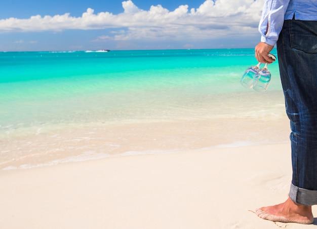 Nahaufnahme von zwei weingläsern in der hand eines mannes auf dem weißen sandigen strand