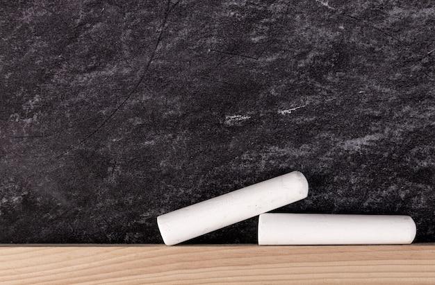 Nahaufnahme von zwei weißen kreidestücken auf tafel
