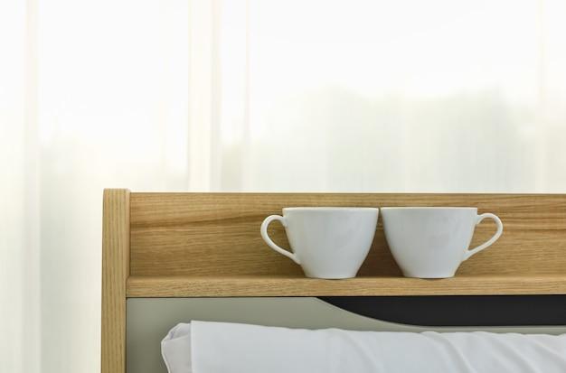 Nahaufnahme von zwei weißen tasse heißen kaffee auf dem regal über dem bett am morgen im schlafzimmer.