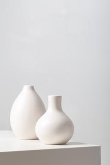 Nahaufnahme von zwei weißen tonvasen auf dem tisch unter den lichtern auf weiß