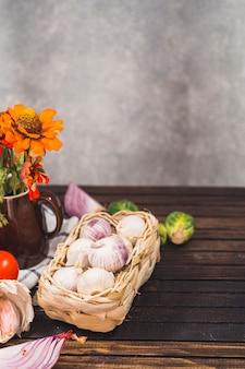 Nahaufnahme von zwiebeln; rosenkohl; knoblauchzehen; blumen und stoff auf holzoberfläche