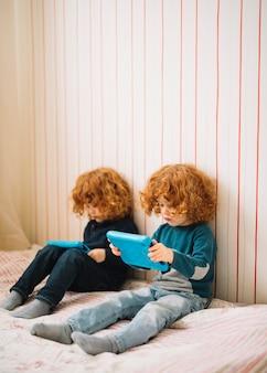 Nahaufnahme von zwillingen mit dem roten vorangegangenen haar, das digitale tablette betrachtet