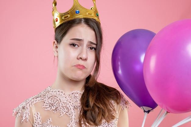 Nahaufnahme-vorderansicht enttäuschtes mädchen mit krone, die ballons hält