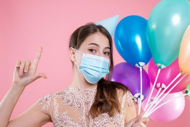 Nahaufnahme-vorderansicht-partygirl mit krone und maske, die ballons hält, die fingerpistole machen