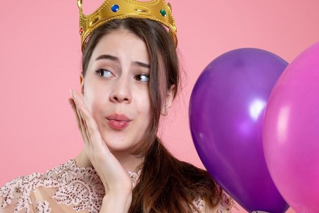 Nahaufnahme-vorderansicht verwirrte partygirl mit krone, die ballons hält