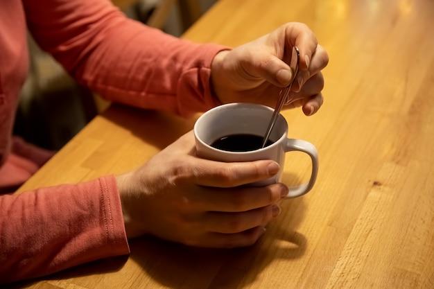 Nahaufnahme weibliche hände halten eine weiße tasse mit einem warmen getränk und mischen mit einem teelöffel auf einem holztisch