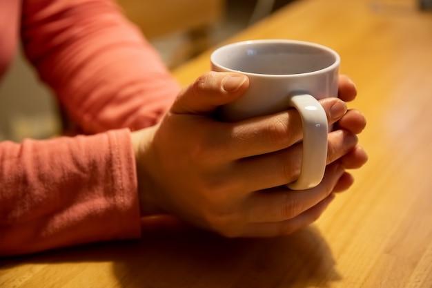 Nahaufnahme weibliche hände halten und umarmen eine weiße tasse mit einem warmen getränk auf einem holztisch das konzept von