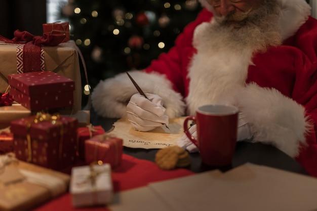 Nahaufnahme weihnachtsmann, der einen brief schreibt